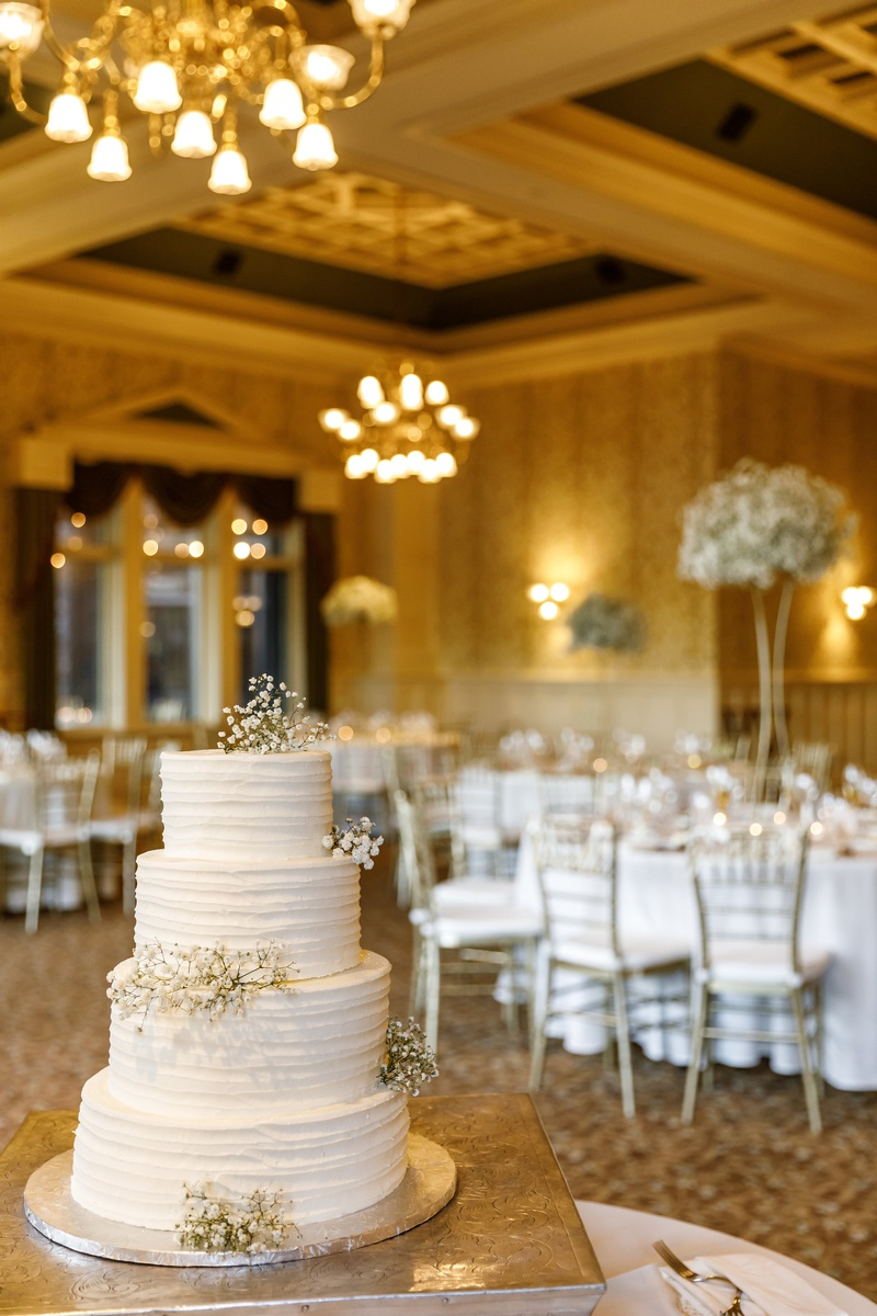 Four tier wedding cake with sprigs of baby's breath