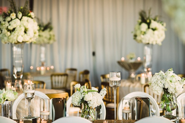 Wedding reception white drapery white rim round back chairs gold linens white hydrangea centerpieces