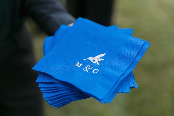 Cocktail napkins in royal blue printed with hummingbird and bride and groom's monogram