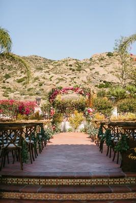 wedding ceremony outside hummingbird nest ranch terracotta tile pink greenery bougainvillea arch