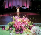 Green table topped with orchids and candles