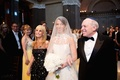 Mother of bride and father of bride walks bride down aisle