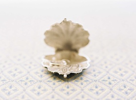 Round diamond engagement ring with square halo in scallop shell jewelry holder