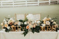 wedding sweetheart table with gold mr. and mrs. letters, peach floral garland with greenery and a gl