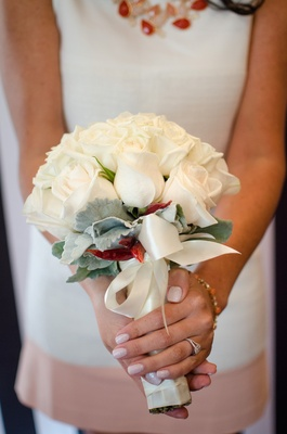 Bride's wedding shower bouquet of white roses, greenery, red chilies, tied in white satin ribbon