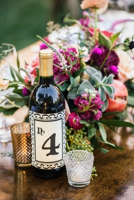 Outdoor bohemian wedding reception table with table number on wine bottle label, votive candles