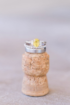 Yellow diamond oval engagement ring and eternity band on top of champagne cork