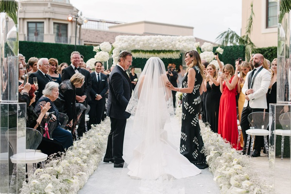 Bride in veil and oscar de la renta wedding dress with father mother guests watching
