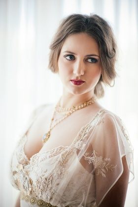 Bride in a Claire Pettibone dress with gold and silver embroidery, with gold and pearl necklace