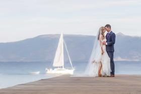 bride groom pose dock lake tahoe sailboat long veil blue suit purple tie