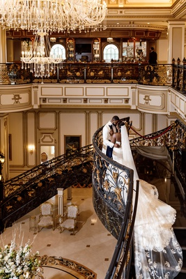 bride in wedding dress long train lace veil with groom at legacy castle in new jersey