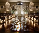 Large altar trees, chuppah, and candle-lined aisle