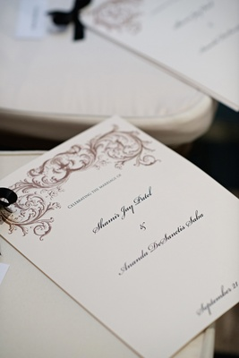 Ceremony booklet tied with black ribbon on chair