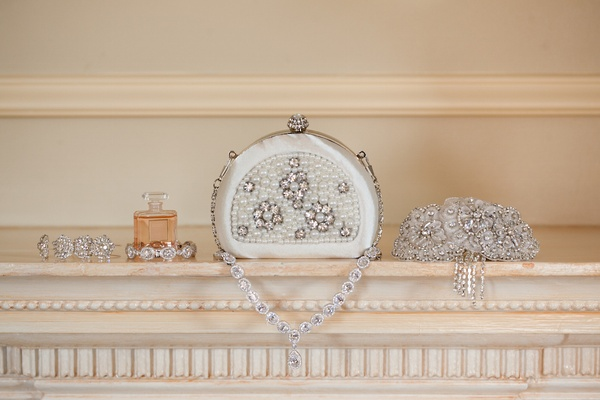 Bride's satin minaudiere decorated with crystals and pearls sits next to sparkling bracelets