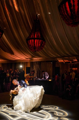 Groom dips bride on dance floor at barn wedding reception