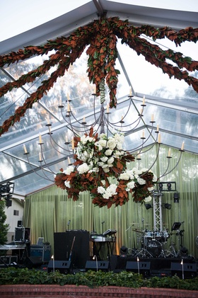 Wedding band stage at at home wedding reception with Southern magnolia leaf garland decorations
