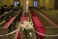 Red tufted church pews with white flower arrangement