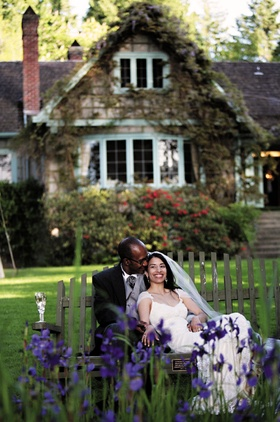 Bride in a Claire Pettibone lace gown and veil with groom in black tails sit on a bench