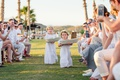 flower girls with wide baskets in long white dresses and flower crowns, guests take pictures