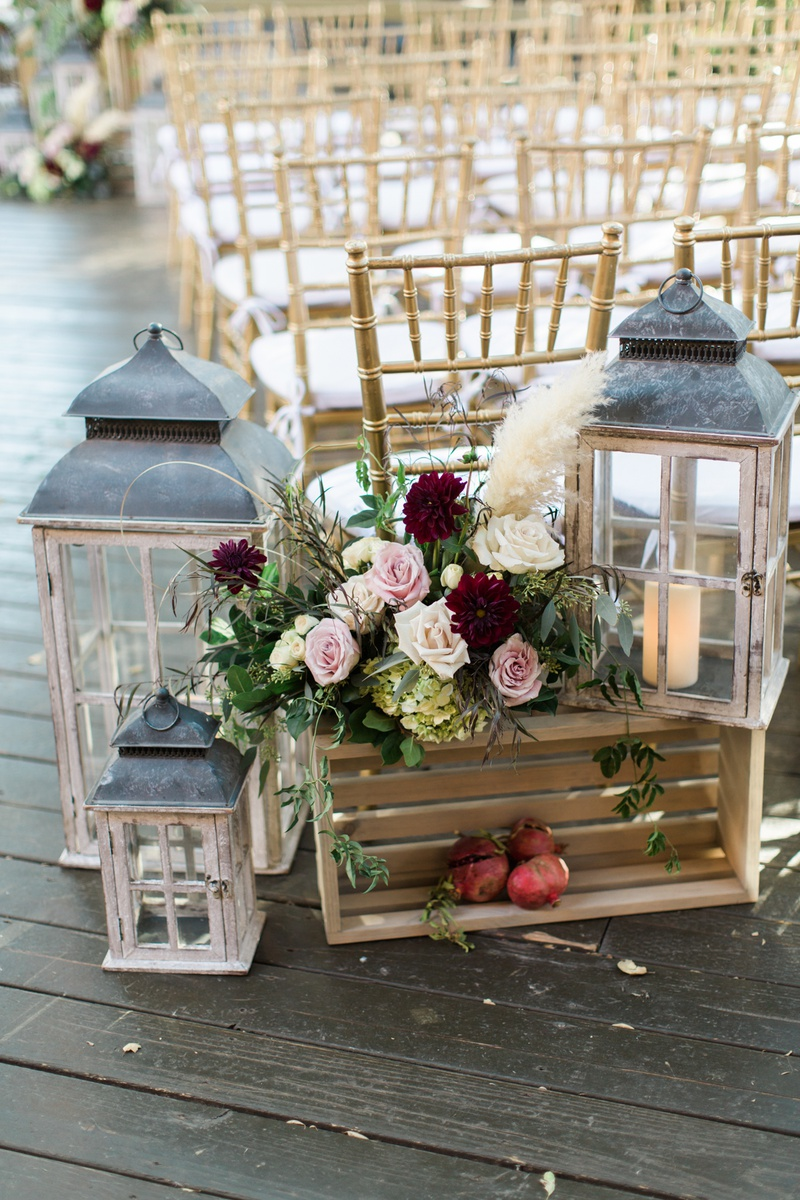 rustic fall ceremony decor with lanterns, blush roses, wine red dahlias, pampas grass, pomegranates