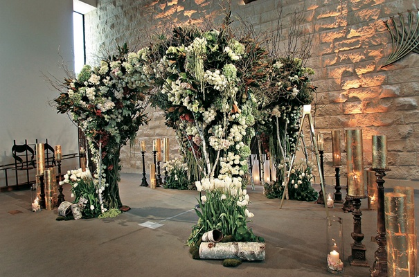 Gold candles surrounding floral-embellished chuppah