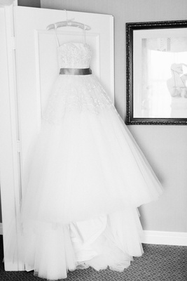 strapless ball gown with tulle skirt hanging on door