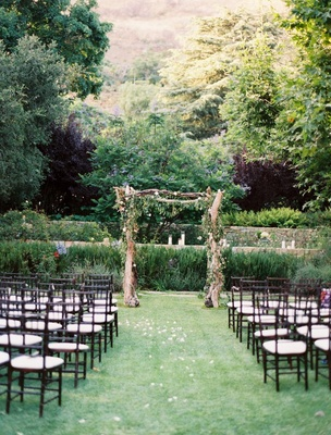 Outdoor wedding ceremony with an altar made of driftwood and greenery