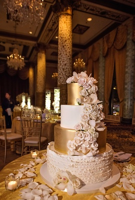 white gold and blush four tier wedding cake with cascading flowers on gold table linens