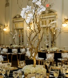 wedding reception centerpiece with gold manzanita branches with orchids and crystals