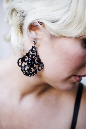 Bridesmaid wears black filigree earring with skull center