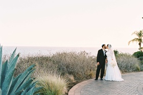 Bride in Alfred Angelo wedding dress groom in tuxedo at Terranea wedding venue in California