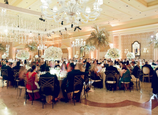wedding reception guests sitting at tables palm trees chandeliers ballroom the breakers