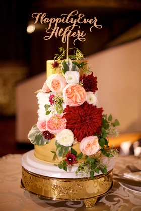 Wedding cake gold with white ruffle layer happily ever after cake topper and fresh flowers red blush