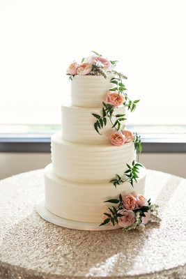 four tiered wedding cake with buttercream frosting, blush garden roses, greenery