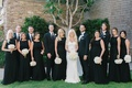 Bride in a Galia Lahav gown with lace panels, groomsmen, bridesmaids in sleeveless black dresses