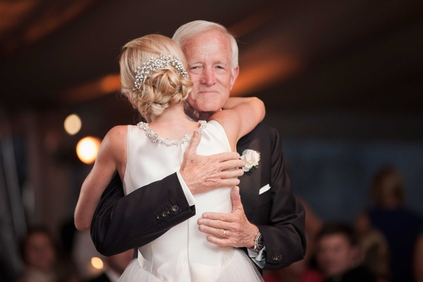 a blushing bride hugs her father after their father daughter dance at her wedding reception
