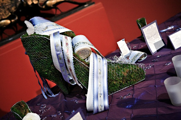 Metal shoe mold filled with grass and decorated with floral ribbons and butterfly appliqué