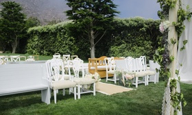 Vintage benches and chairs at outdoor grass wedding