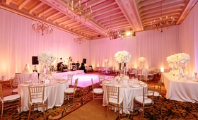 Pink lighting in ballroom wedding reception room with white flowers, live band