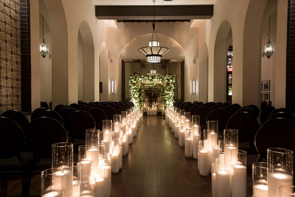 hotel figueroa wedding ceremony long aisle with candles in hurricane vases greenery white flower arc
