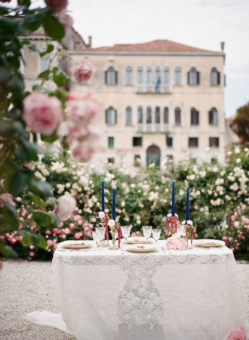 Destination wedding elopement in venice italy intimate dinner lace table linen and tall blue candles