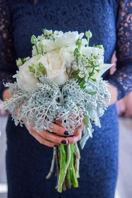 Bridesmaid in blue lace dress holding white rose bouquet