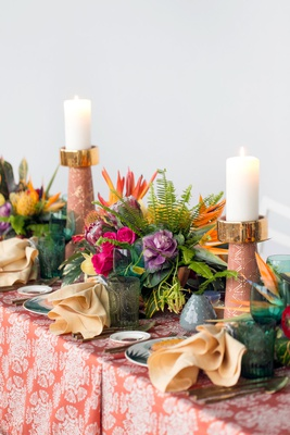 wedding reception styled shoot green glassware tall candlesticks orange pattern linen bird