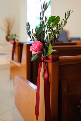 Catholic ceremony wood pew with floral bouquet