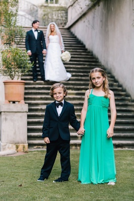 Ring bearer in black tuxedo and bow tie with flower girl in long green tank dress braid