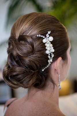 Back of bride's updo with pearl headpiece on side