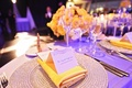 Wedding reception place setting with silver charger, yellow napkin, place card with circular design
