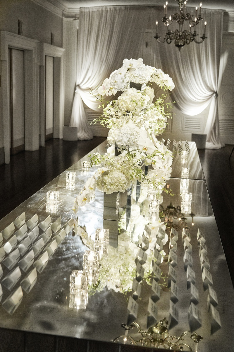 White floral arrangements on mirror tabletop