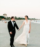 Bride in v neck lace wedding dress with groom holding hands with sand on beach in Georgia