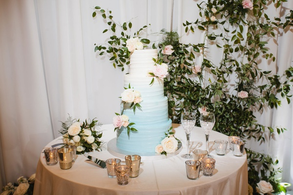 wedding cake on table next to sweetheart table greenery drapery light blue to white ombre colors
